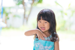 Adorable Asian baby girl in blue dress, on white and green backg Royalty Free Stock Images