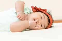 Adorable asian baby sucking thump on the bed. Royalty Free Stock Photography