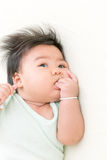 Adorable asian baby sucking thump on the bed. Stock Images