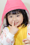 Adorable Asian girl. Pick her nose, closeup portrait of funny expression on face Royalty Free Stock Photos