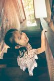 Asian girl smiling and coming down wooden stairs at home. Vintag Stock Image