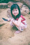 Adorable asian girl has fun digging in the sand on a summer day. Royalty Free Stock Image