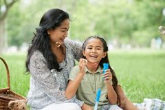 Asian girl blowing bubbles on picnic with mother. Adorable Asian girl laughing and blowing bubbles while spending time with mother on picnic in park royalty free stock photo