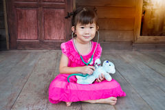 Adorable asian girl playing doctor or nurse with plush toy bear Stock Photo