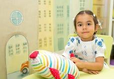 Adorable asian, Kazakh child girl in nursery room. Kid in kinder Stock Photo