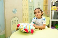Adorable asian, Kazakh child girl in nursery room. Kid in kindergarten in Montessori preschool class. Stock Image