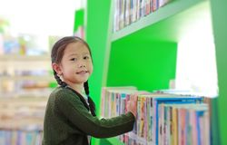 Adorable Asian little girl looking for book on bookshelf at library. Child reaches for books on a shelf royalty free stock photography