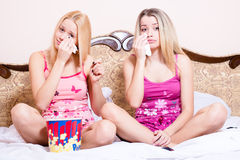 2 adorable attractive pretty young blond women sitting in bed with popcorn, watching movie and crying stock photography