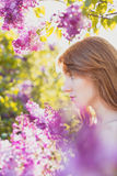 Adorable Attractive redheaded woman. Attractive redheaded woman profile look at side. blossoming violet lilacs. Hot summer mood. Bright backlight Stock Photos