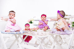Tea party. Adorable babies group having tea party stock photos
