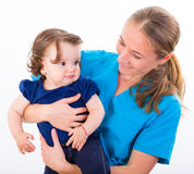 Adorable baby and babysitter. Babysitter holding in arms an adorable baby girl Stock Photo