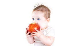 Adorable baby with big blue eyes eating red apple Stock Photo