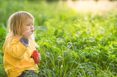 Adorable baby blow soap bubbles in park Royalty Free Stock Photos
