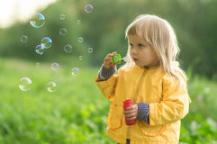 Adorable baby blow soap bubbles in park Stock Photos
