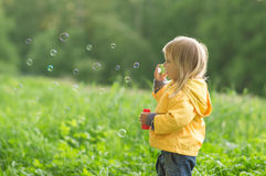 Adorable baby blow soap bubbles in park Stock Images