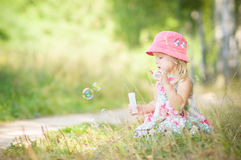 Adorable baby blow soap bubbles in park Royalty Free Stock Photo