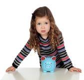 Adorable baby with a blue money-box Stock Photos
