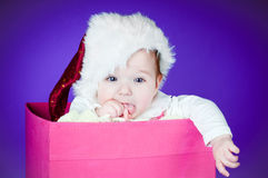 Adorable baby in a box wearing santa hat Royalty Free Stock Photography