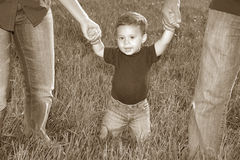 Adorable Baby Boy. Baby Boy walking in a field holding his parents' hands Royalty Free Stock Photo
