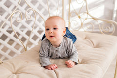 Adorable baby boy in beige sunny bedroom. Newborn child relaxing. Nursery for young children. Textile for kids. Family Stock Photography