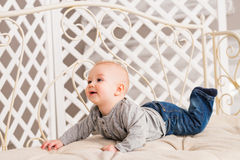 Adorable baby boy in beige sunny bedroom. Newborn child relaxing. Nursery for young children. Textile for kids. Family Royalty Free Stock Photo