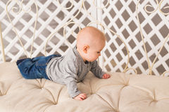 Adorable baby boy in beige sunny bedroom. Newborn child relaxing. Nursery for young children. Textile for kids. Family Stock Image
