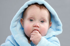 Adorable baby boy in a blue bathrobe Stock Image
