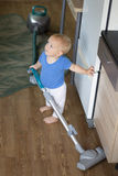 Adorable baby boy cleaning up the kitchen with hoover Stock Photo