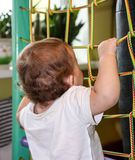 9 month baby boy climbs on the net. Adorable baby boy climbs on the net Royalty Free Stock Photography