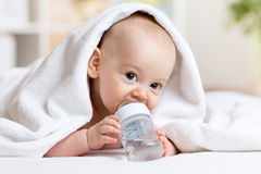 Adorable baby boy drinks water from bottle wrapped Royalty Free Stock Image