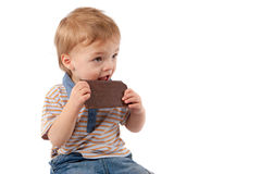 Adorable baby boy eating chocolate. Royalty Free Stock Photography