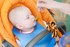 Adorable baby boy first time eating meal Stock Photos