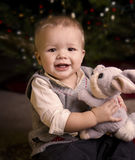 Adorable baby boy holding a toy. Adorable baby boy in front of a Christmas tree holding a toy Stock Photos