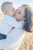 Adorable baby boy kissing his pretty young mather outdoor at summer day. Family dressed in national white clothes. Adorable baby boy kissing his pretty young Royalty Free Stock Photography