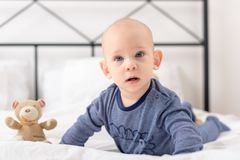 Adorable baby boy lplaying with toy bears on a bed. Newborn child relaxing. Adorable baby boy lplaying with toy bears on a bed. Newborn child relaxing in bed Royalty Free Stock Photos