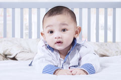 Adorable baby boy lying on bedroom Stock Images