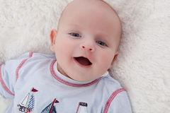 Adorable baby boy lying on fur blanket smiling Stock Photos