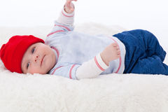 Adorable baby boy lying smiling with red hat on Stock Image