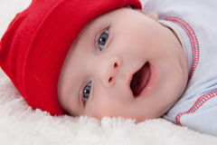 Adorable baby boy lying smiling with red hat on Royalty Free Stock Photo