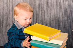 Adorable baby boy with a pile of books Stock Photos