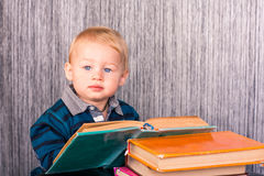 Adorable baby boy with a pile of books Royalty Free Stock Images