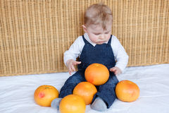Adorable baby boy playing with oranges Stock Photography