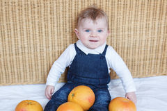 Adorable baby boy playing with oranges Royalty Free Stock Image