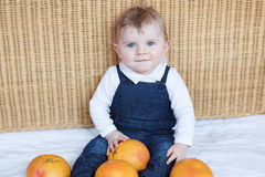Adorable baby boy playing with oranges Stock Images