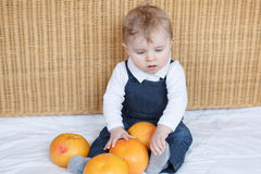 Adorable baby boy playing with oranges Stock Image