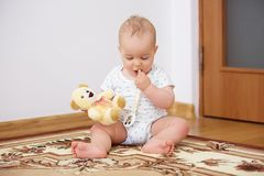 Adorable baby boy playing with plush toy in badroom. In sunny day royalty free stock image