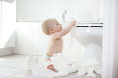 Adorable baby boy playing with toilet paper Stock Image