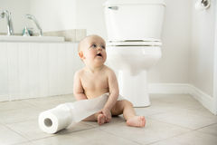 Adorable baby boy playing with toilet paper Stock Photos
