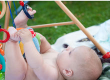 Adorable baby boy playing with toys in summer Stock Photos