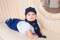 Adorable baby boy in the room. Newborn child relaxing on the couch. Nursery for young children. Family morning at home. Royalty Free Stock Images